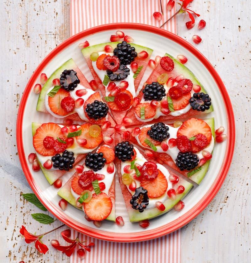 西瓜比萨、素食主义者、果子比萨用乳脂状的自然酸奶和新鲜水果在一块板材,在一张白色木桌上,顶面v 免版税库存图片