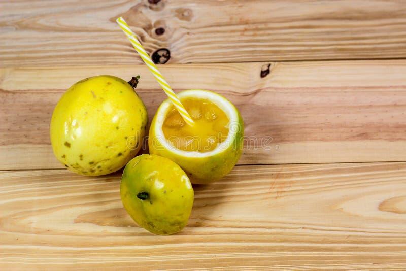 西番莲果一半和汁液在葡萄酒木背景 库存图片
