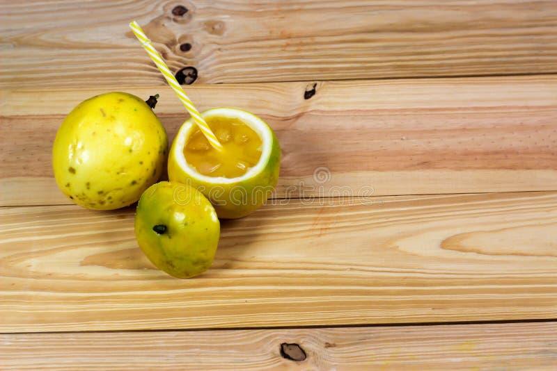 西番莲果一半和汁液在葡萄酒木背景 库存照片