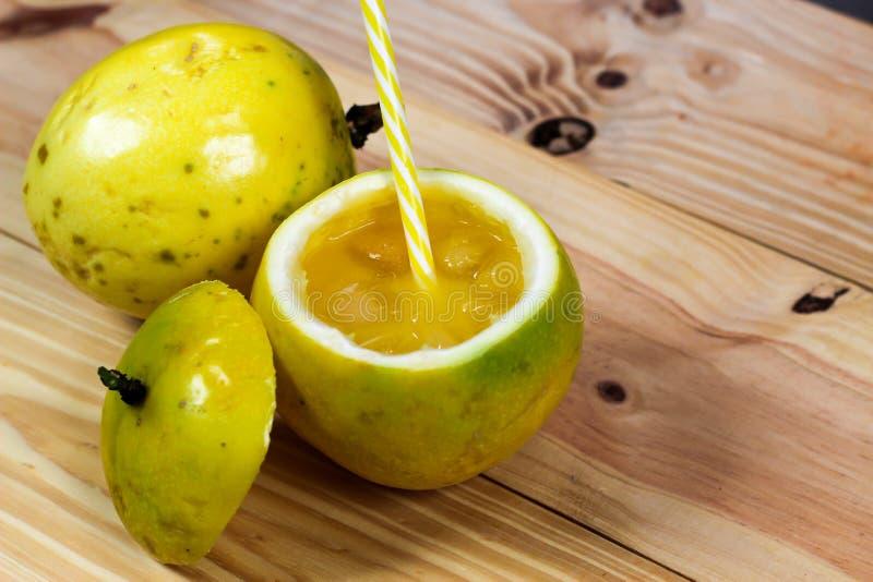 西番莲果一半和汁液在葡萄酒木背景 免版税图库摄影