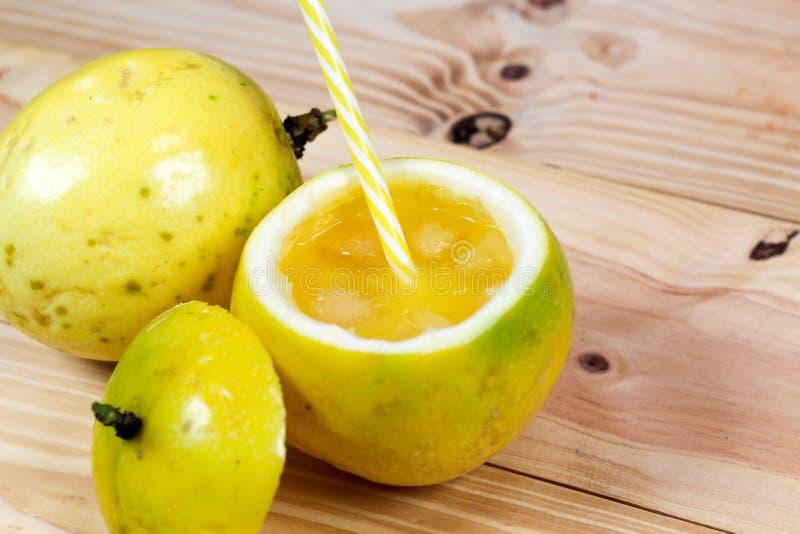 西番莲果一半和汁液在葡萄酒木背景 免版税库存照片