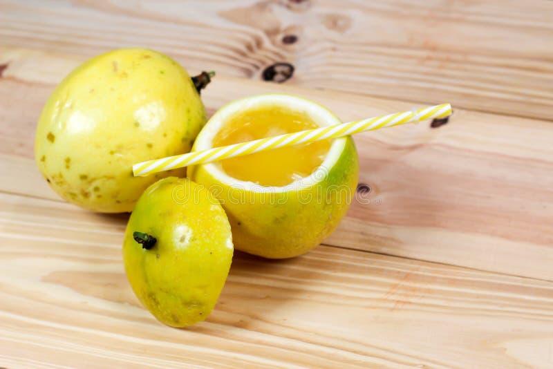 西番莲果一半和汁液在葡萄酒木背景 图库摄影