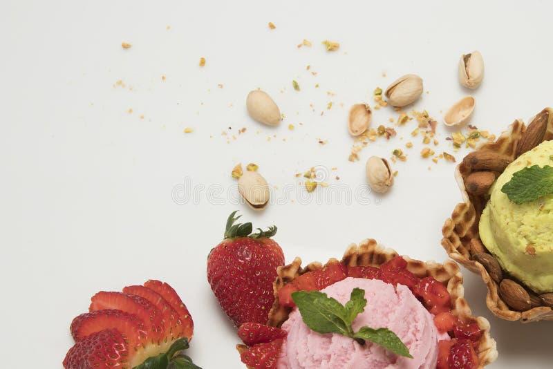 西番莲果和和草莓冰淇淋在篮子白色背景和新鲜水果锥体壳 库存照片