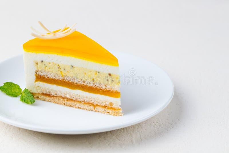 西番莲果蛋糕,在一块白色板材的奶油甜点点心 复制空间 图库摄影