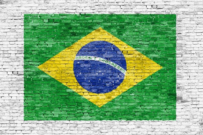 巴西的旗子在白色砖墙上绘了 库存照片