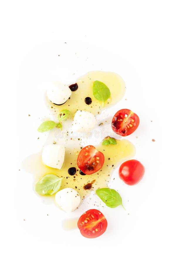 西红柿、无盐干酪乳酪、蓬蒿和橄榄油在白色 免版税库存图片