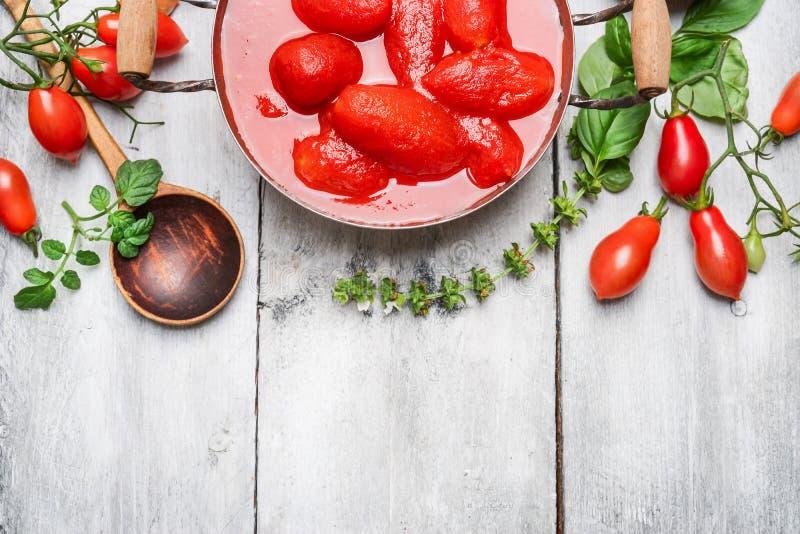 西红柿酱-新鲜和被剥皮的蕃茄、蓬蒿和匙子的成份在白色木背景,顶视图 免版税库存图片