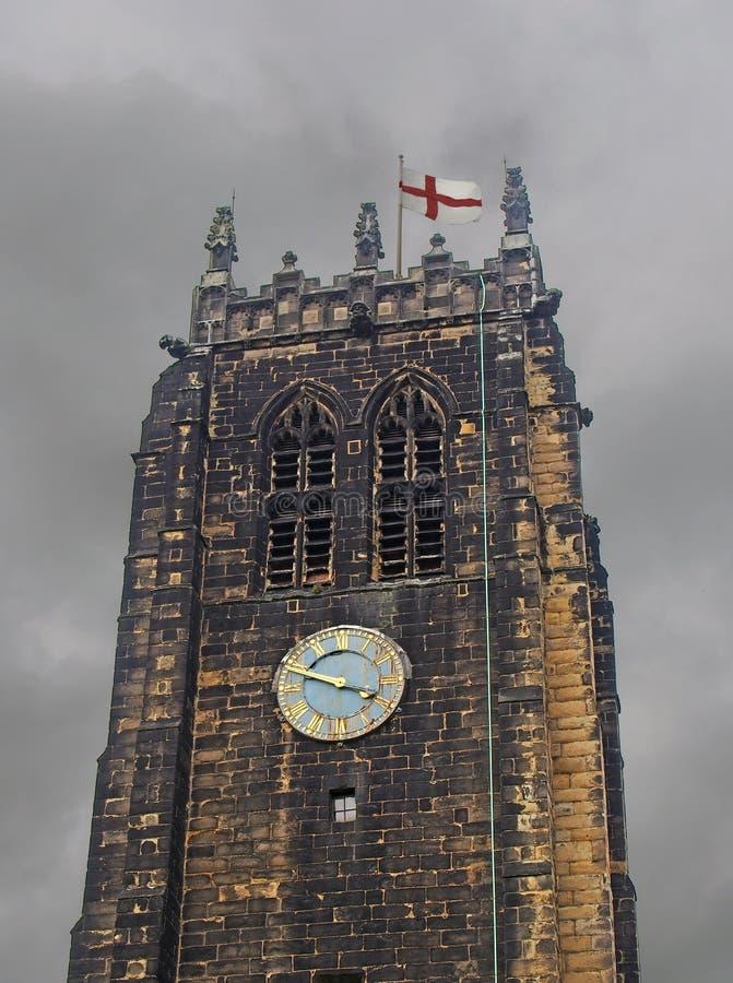 西约克郡哈利法克斯大教堂的塔楼和钟楼,对面一片灰色的多云天空,并悬挂英国国旗 免版税库存照片