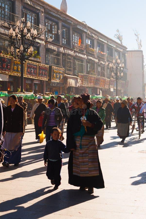 西藏母亲儿童拉萨走的Barkhor人群 免版税库存图片