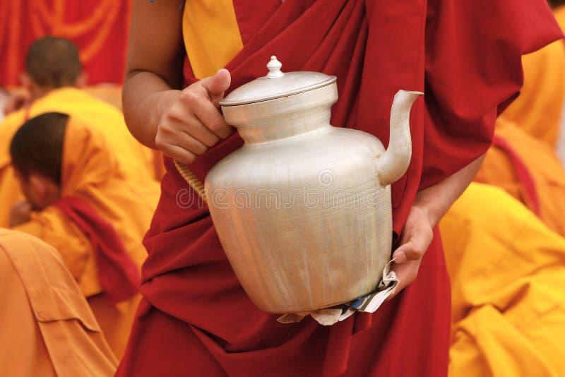 西藏茶茶壶在一名修士的手上在尼泊尔 免版税库存照片