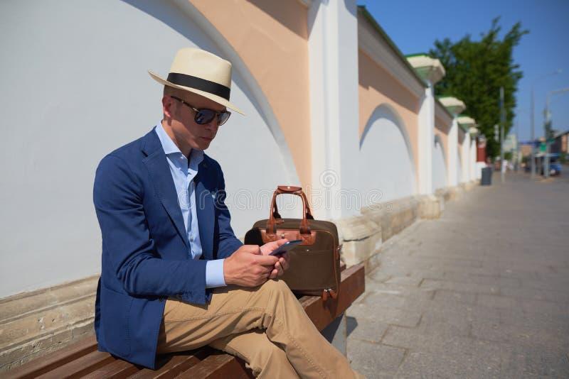 西装的一个人坐长凳和谈话在电话 免版税库存图片