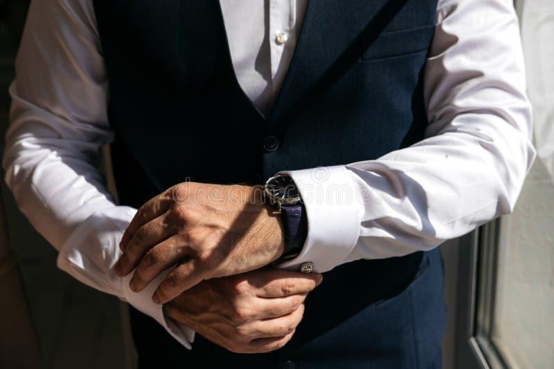 西装的一个人用拉锁拉上衬衣袖口 免版税图库摄影