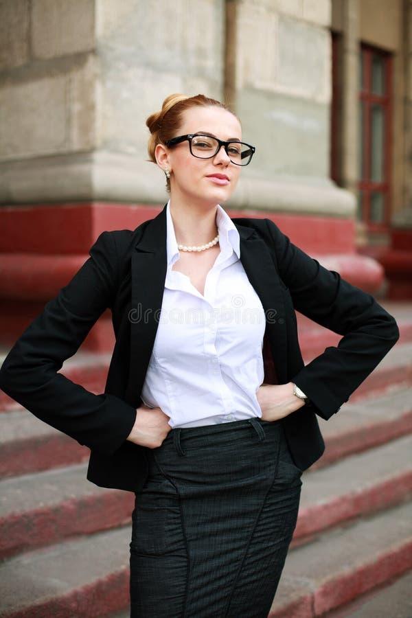 西装的严肃的女学生在大学前面 免版税图库摄影