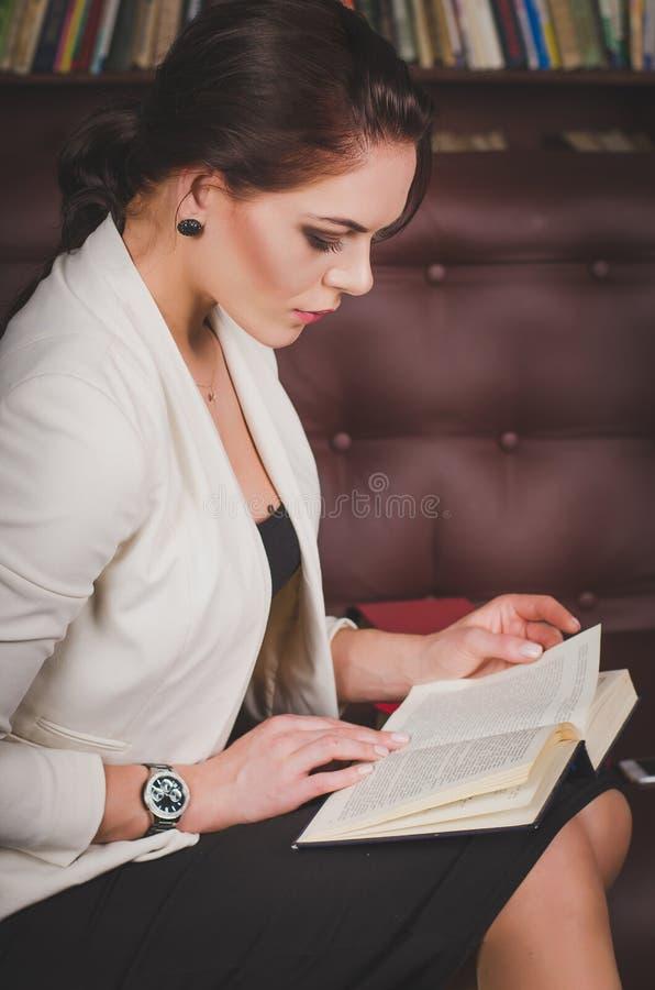 西装的可爱的女商人坐leathe 库存照片