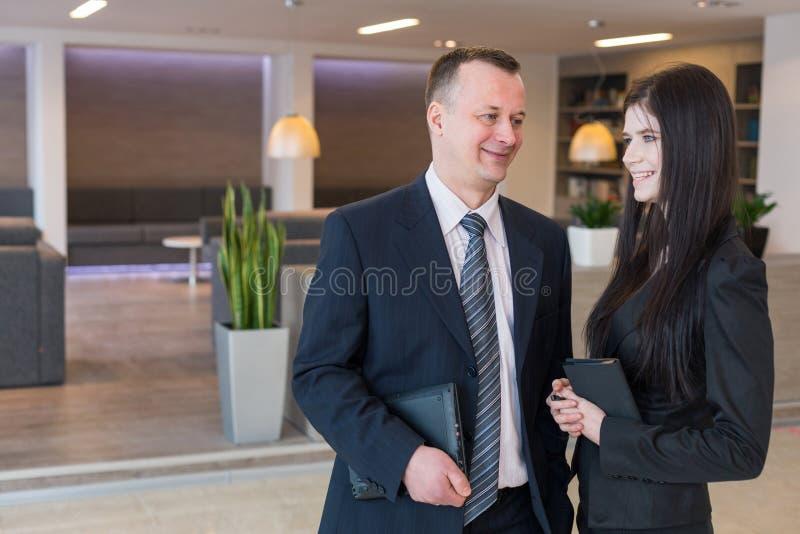 西装的同事谈话在办公室 免版税图库摄影