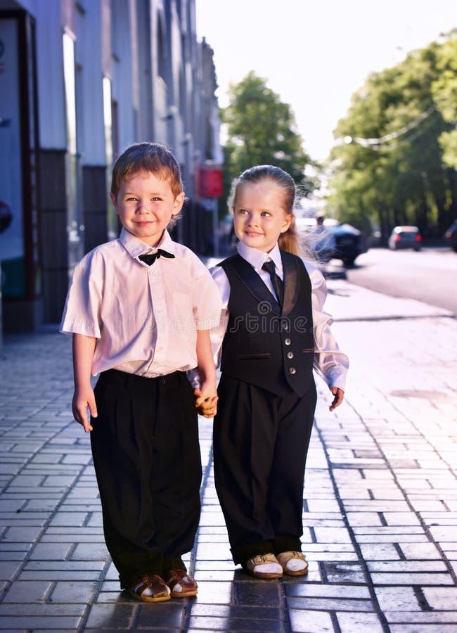 西装的孩子在中心室外城市街道 免版税图库摄影