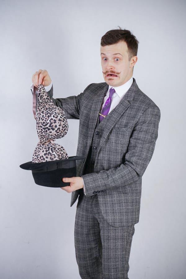 西装的年轻人拔出从他的帽子的豹子胸罩,但是他想要与奇迹和财富的把戏 情感男性感觉 免版税图库摄影