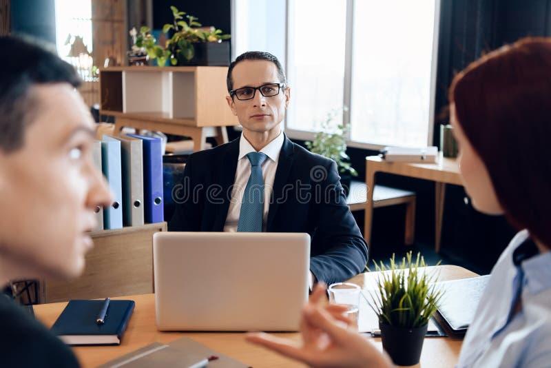 西装的律师在办公室坐,听关于与离婚的夫妇的讨论 免版税库存照片