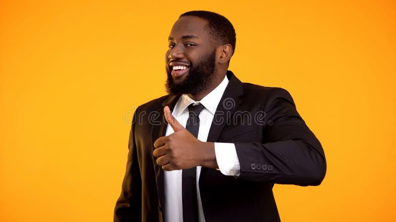 西装的微笑的黑人在做翘拇指和看对凸轮的衣服 库存照片
