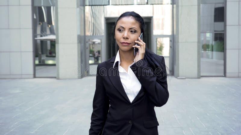 西装的自信成功的妇女谈话在电话,事务 免版税库存照片