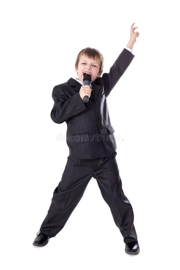 西装的逗人喜爱的小男孩有话筒唱歌孤立的 库存照片