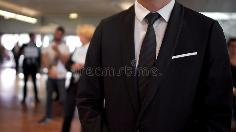 西装等待的到来的人在机场大厅里,旅行代理人,旅游业 库存照片