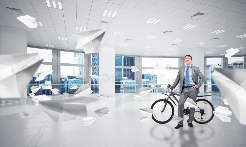 西装身分的微笑的人与自行车 免版税库存图片