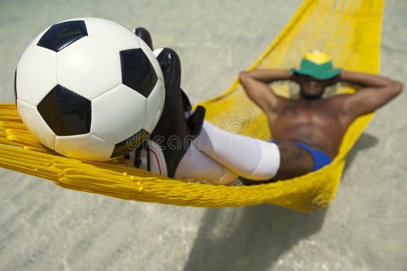 巴西足球运动员放松与在海滩吊床的橄榄球 库存图片