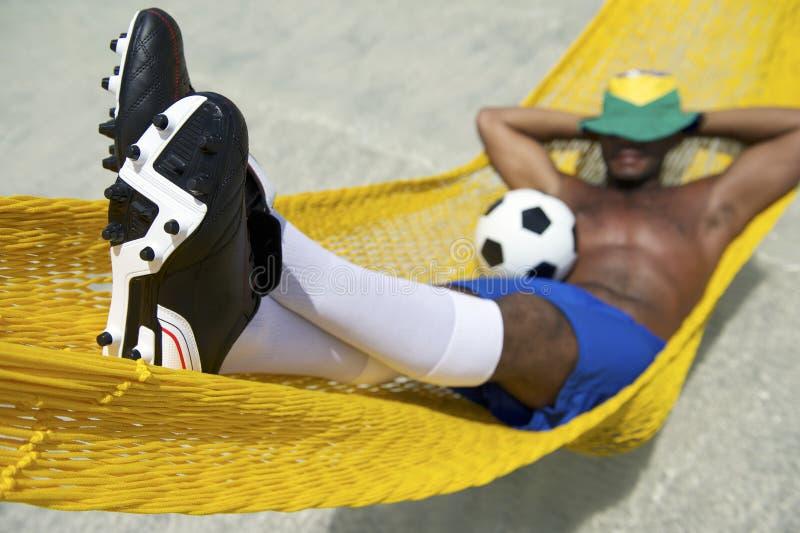 巴西足球运动员放松与在海滩吊床的橄榄球 免版税库存照片