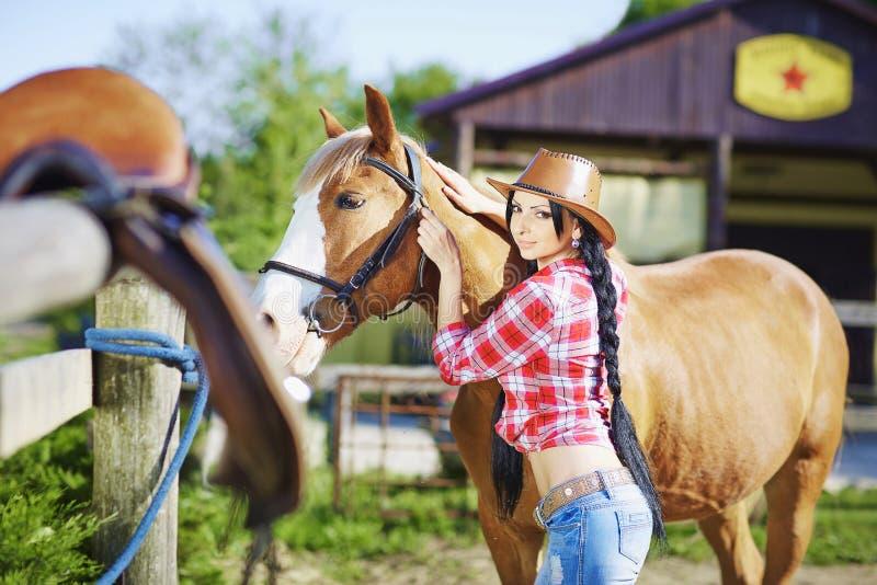 西部样式的画象性感的女牛仔与hors 免版税库存照片