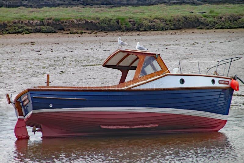 西顿,德文郡,英国- 2012年5月22日:一小渔船在它的边处于低潮中说谎在河轴出海口 两只海鸥 库存照片