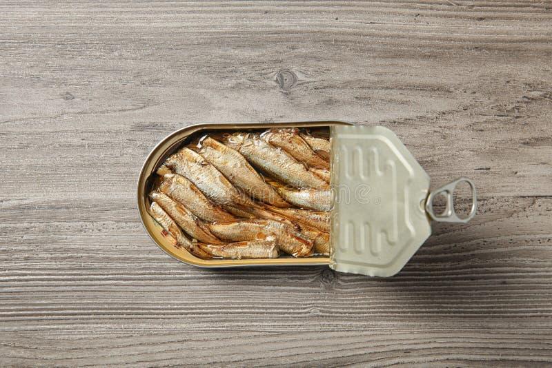 西鲱开放锡罐在木背景的 免版税图库摄影