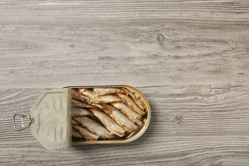 西鲱开放锡罐在木背景的 免版税库存图片