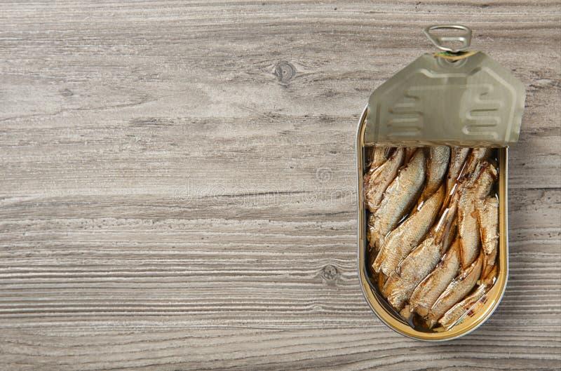 西鲱开放锡罐在木背景的 r 免版税库存图片