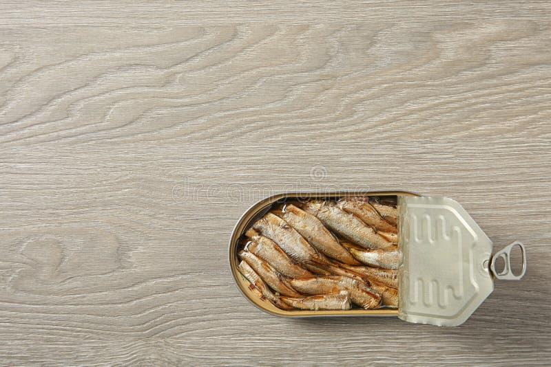 西鲱开放锡罐在木背景的 r 图库摄影