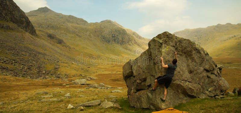 要做Bouldering的岩石的登山人在湖区,英国 库存图片