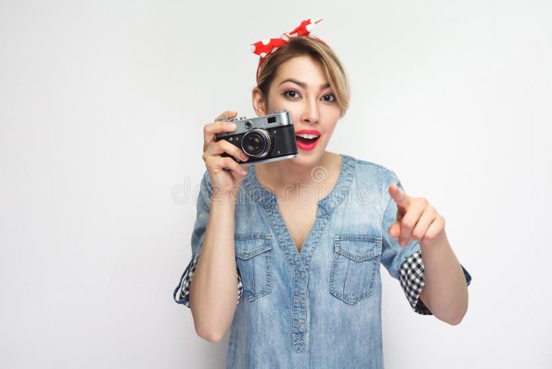 要做photoshout 偶然牛仔布衬衣的年轻博客作者女孩有构成,红色头饰带身分的,拿着减速火箭的照相机和 库存照片