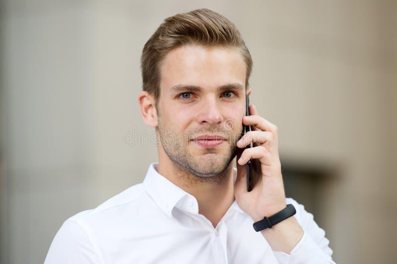 要求信息 称的商人客户举行智能手机都市背景defocused 人经理通话 免版税库存图片