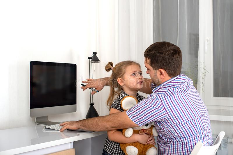 要求的少女的演播室情感射击一个繁忙的人计算机爸爸给予她的关注并且使用与她 免版税库存图片