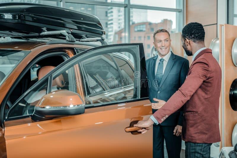 要求的顾问他的客户坐在汽车 免版税图库摄影