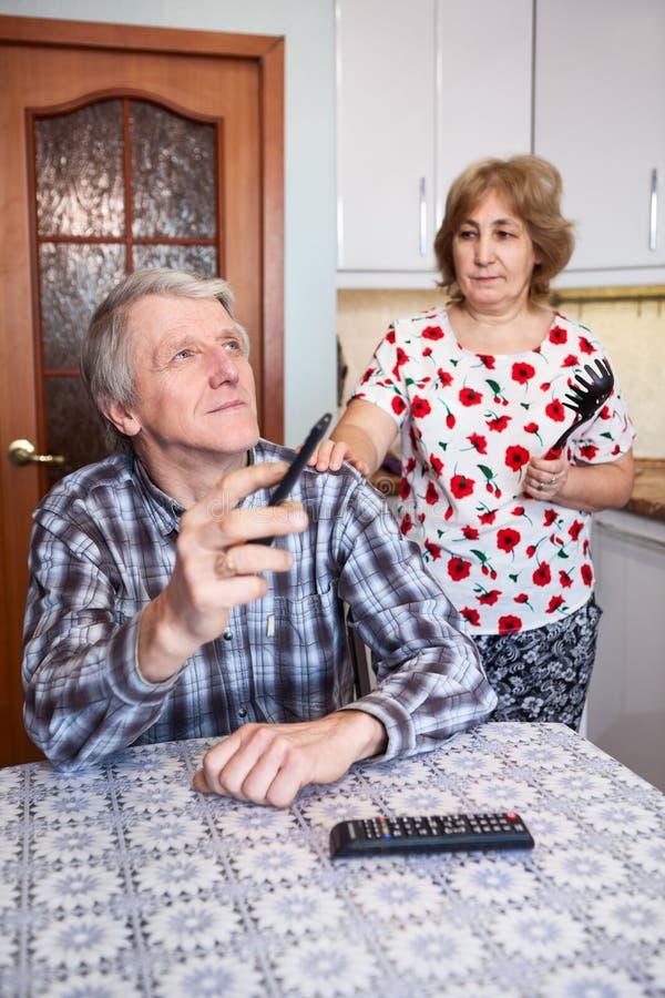 要求资深的妻子懒惰丈夫从看电视逃脱在厨房里,成熟夫妇关系 免版税库存图片