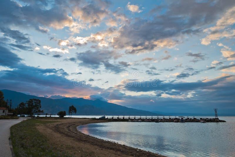 覆盖反射在爱琴海中在日出,有皮立翁山山的沃洛斯港口水在背景中 免版税库存图片