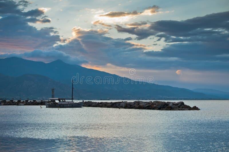 覆盖反射在爱琴海中在日出,有皮立翁山山的沃洛斯港口水在背景中 库存照片