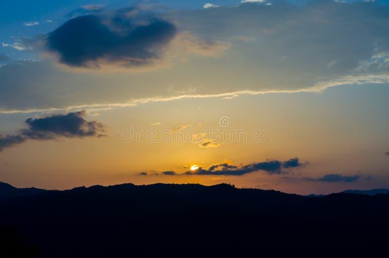 覆盖在山的天空日落 免版税库存照片