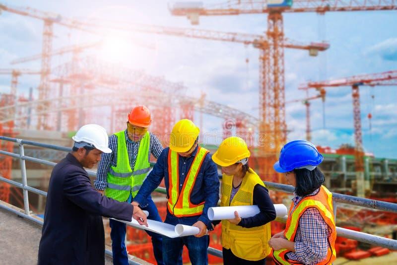 见面为专业工程师成功的项目建筑队的工程师与图纸一起使用 库存照片