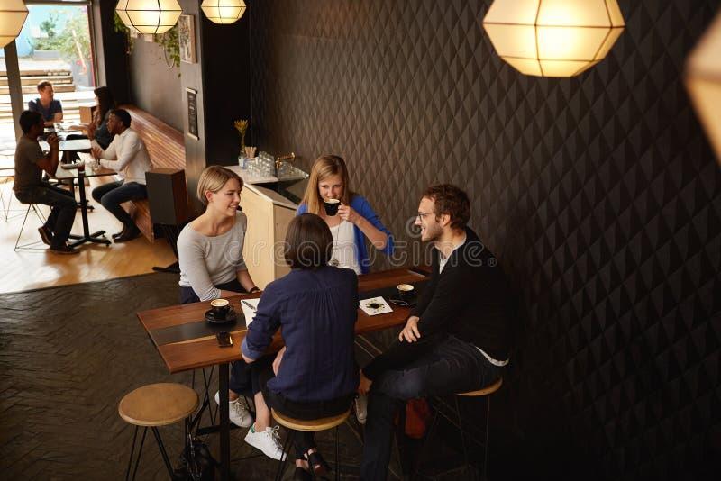 见面为在咖啡店的cappucinos的小组朋友 图库摄影