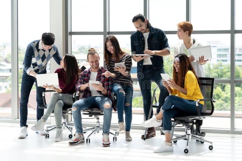 见面和群策群力在办公室的愉快的商人不同种族的队  免版税库存照片