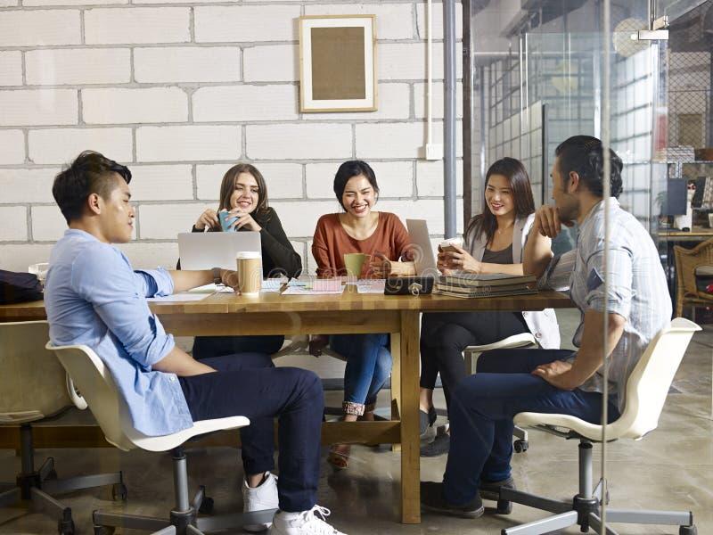见面在办公室的亚裔和白种人企业家队  免版税库存图片