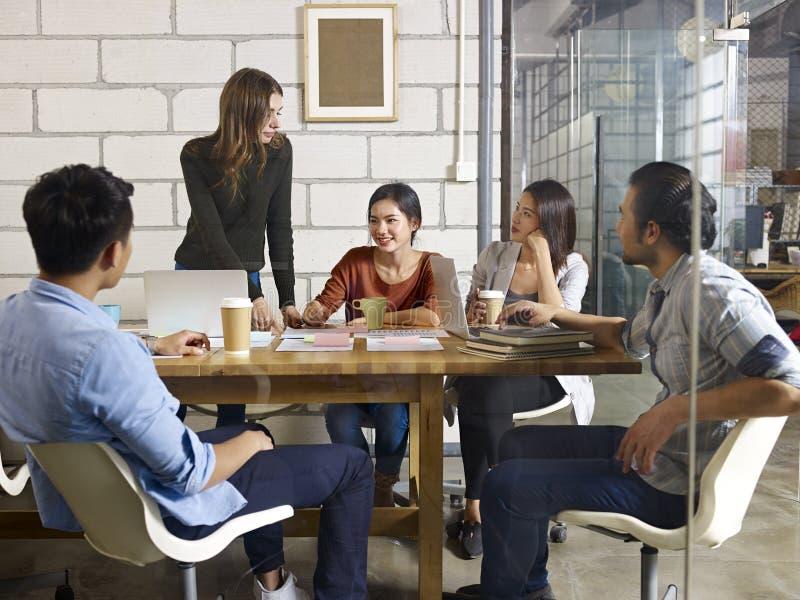 见面在办公室的亚裔和白种人企业家队  库存图片