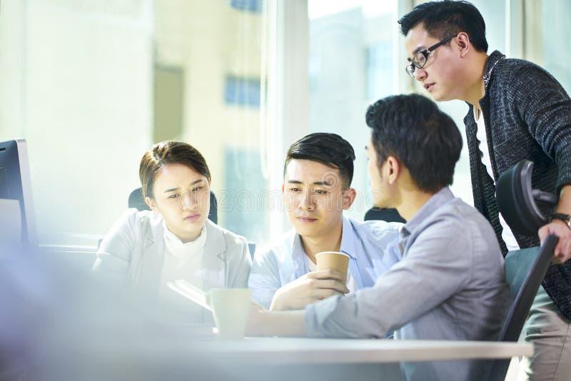 见面在办公室的年轻亚裔商人 免版税库存图片